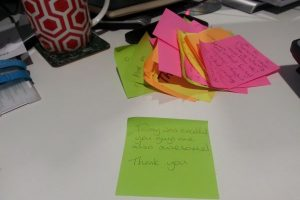 Post it note with some writing on it.